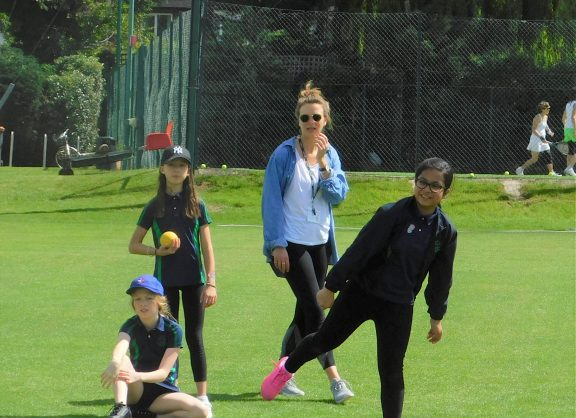 Girls and staff watching their friends compete in sports day