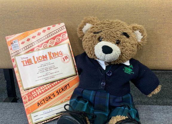 Lion King script next to the school bear, Miss Ivy
